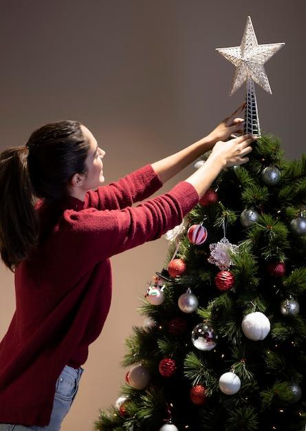 Junge frau der vorderansicht, die weihnachtsbaum verziert Kostenlose Fotos