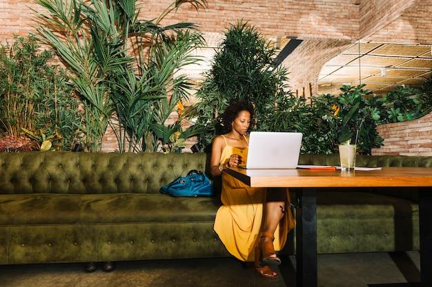 Junge frau des afroamerikaners, die im restaurant unter verwendung des laptops sitzt Kostenlose Fotos