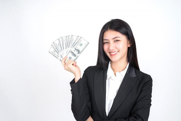 Junge frau des erfolgreichen schönen asiatischen geschäfts, die in der hand geld us-dollar rechnungen hält Kostenlose Fotos