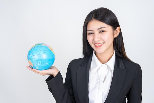 Junge frau des erfolgreichen schönen asiatischen geschäfts, die in der hand weinlesekarte der kugelweltkarte hält Kostenlose Fotos