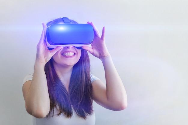 Junge frau des lächelns, die unter verwendung des glassturzhelmkopfhörers der virtuellen realität vr auf weiß trägt Premium Fotos