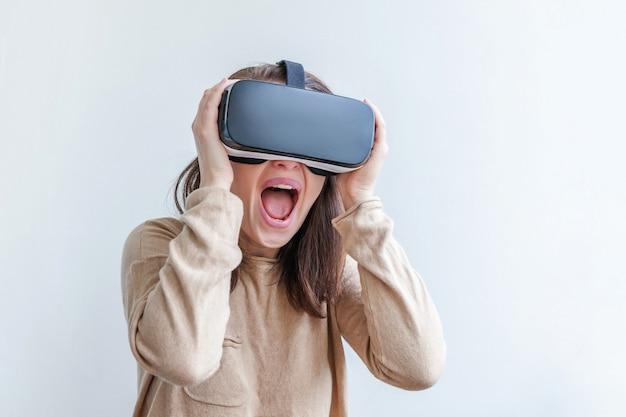 Junge frau des lächelns, die unter verwendung des glassturzhelmkopfhörers der virtuellen realität vr trägt Premium Fotos