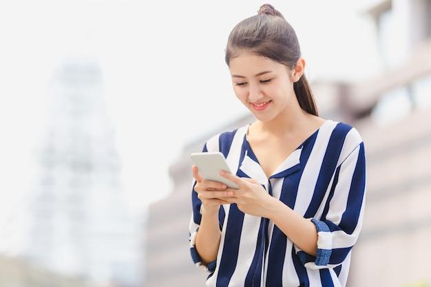 Junge frau des lebensstils im freien, die auf smartphone schaut Premium Fotos