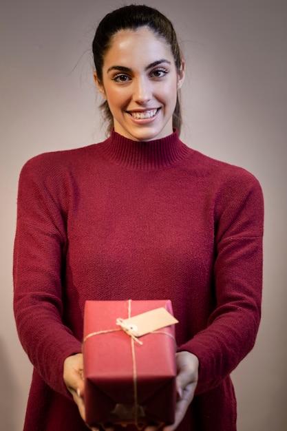 Junge frau des smiley, die weihnachtsgeschenk hält Kostenlose Fotos