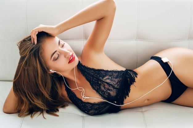 Junge frau, die allein in schwarzen verführerischen dessous auf weißem sofa in tropischer villa liegt und musik auf spieler in kopfhörern lächelnd hört Kostenlose Fotos