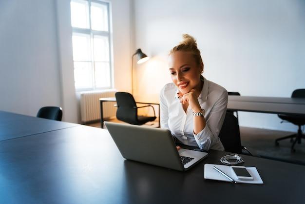 Junge frau, die am modernen schreibtisch mit einem laptop arbeitet Premium Fotos