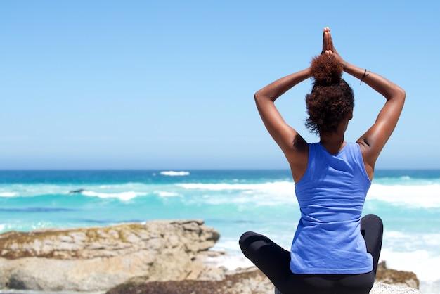 Junge frau, die am strand in der yogahaltung sitzt Premium Fotos