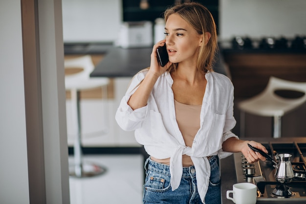 Junge frau, die am telefon spricht und morgenkaffee kocht Kostenlose Fotos