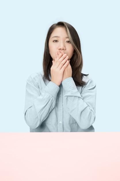Junge frau, die am tisch sitzt, der ihren mund lokalisiert auf blau bedeckt. Kostenlose Fotos