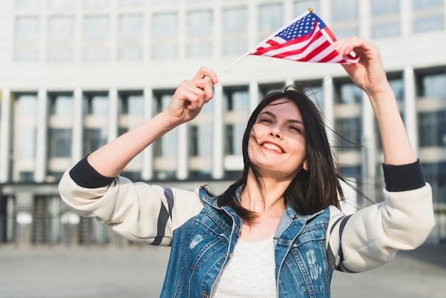 Junge frau, die amerikanische flagge über kopf am vierten juli hält Kostenlose Fotos