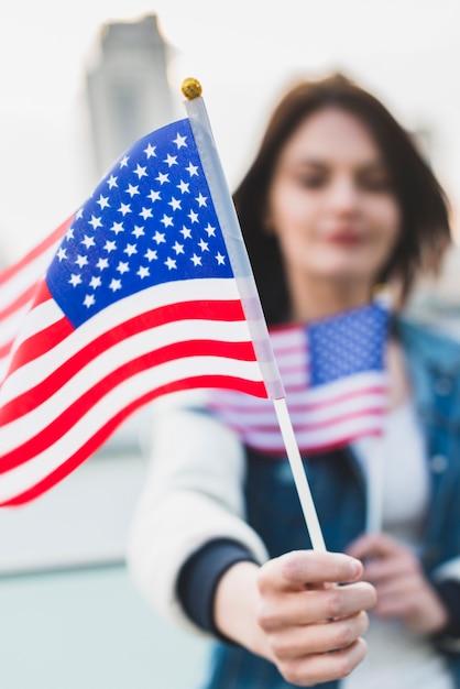 Junge frau, die amerikanische flaggen hält Kostenlose Fotos