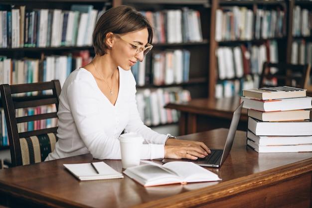 Junge frau, die an der bibliothek unter verwendung der bücher und des computers sitzt Kostenlose Fotos