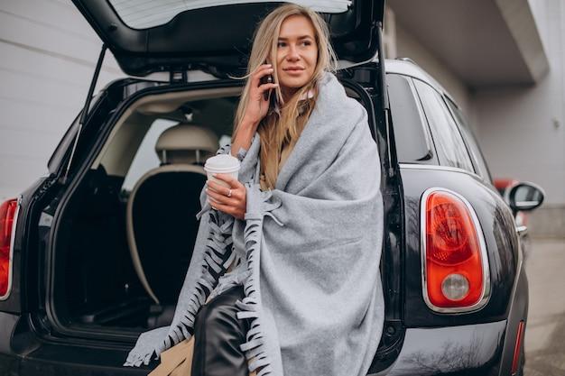 Junge frau, die an ihrem auto steht und kaffee trinkt Kostenlose Fotos