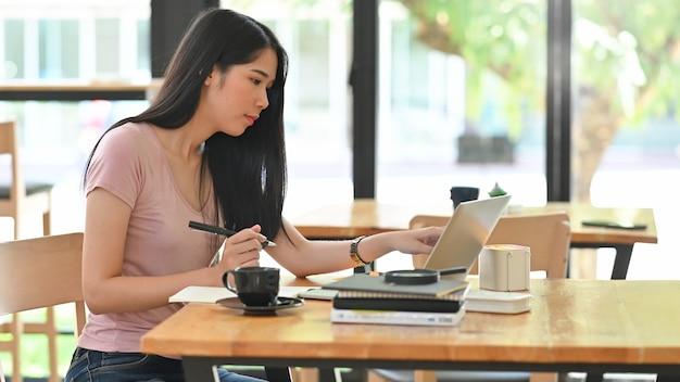 Junge frau, die an laptop arbeitet und stift auf tabelle hält. Premium Fotos