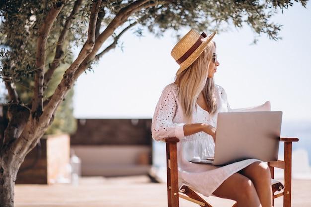 Junge frau, die an laptop auf ferien arbeitet Kostenlose Fotos