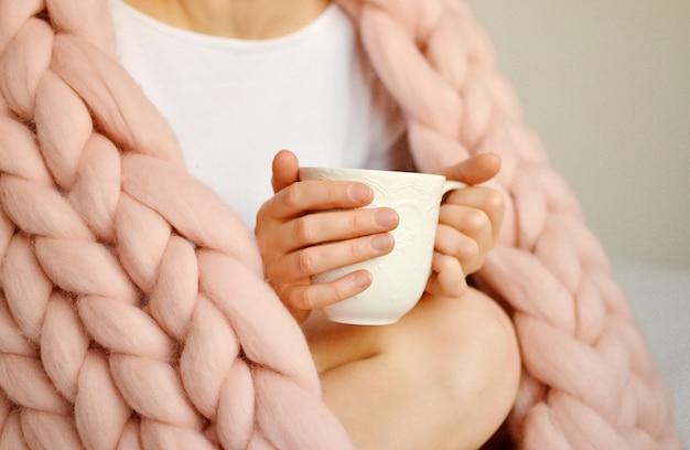 Junge frau, die auf dem bett mit rosa riesiger merino wool plaid-decke mit schale cappuccino sitzt. Premium Fotos