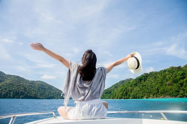 Junge frau, die auf dem boot sich entspannt und vollkommenes meer schaut Premium Fotos
