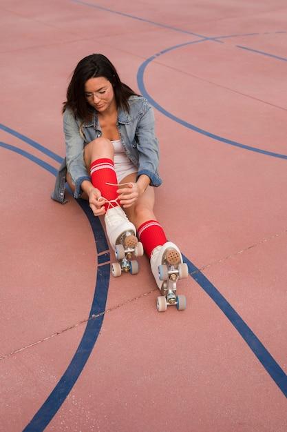Junge frau, die auf dem fußballplatz bindet spitze des rollschuhs sitzt Kostenlose Fotos