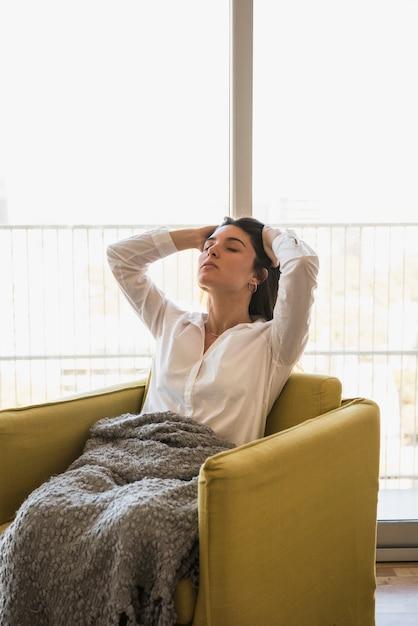 Junge frau, die auf dem lehnsessel sich entspannt im balkon sitzt Kostenlose Fotos