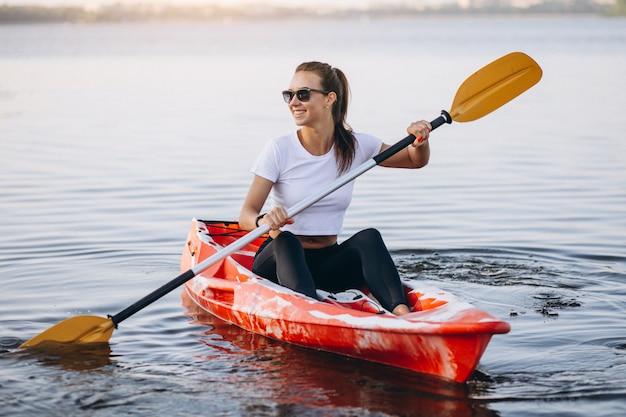 Junge frau, die auf dem see kayak fährt Kostenlose Fotos