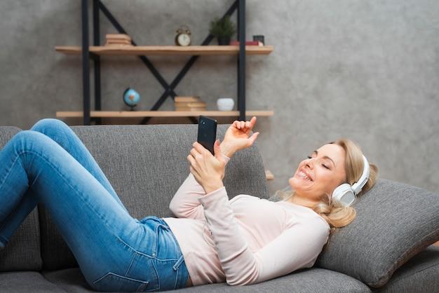 Junge frau, die auf dem sofa genießend liegt, die musik auf kopfhörer von einem intelligenten telefon hörend Kostenlose Fotos