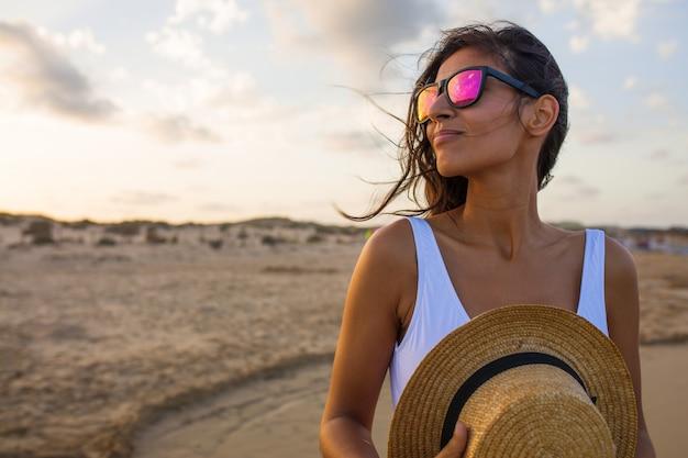 Junge frau, die auf dem strand lächelt Premium Fotos