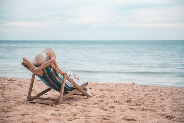 Junge frau, die auf dem strandstuhl, sommerferien-feiertagsreise sich entspannt. Premium Fotos