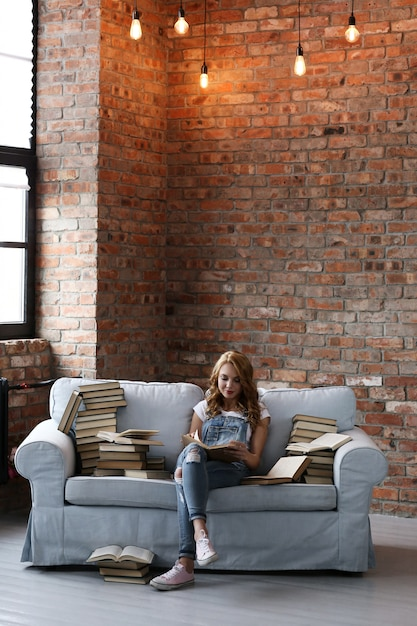 Junge frau, die auf der couch mit vielen büchern ruht Kostenlose Fotos