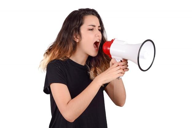 Junge frau, die auf einem megaphon schreit. Premium Fotos