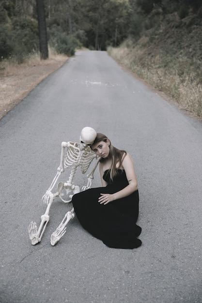Junge frau, die auf leerer straße im wald mit dem skelett sitzt Kostenlose Fotos