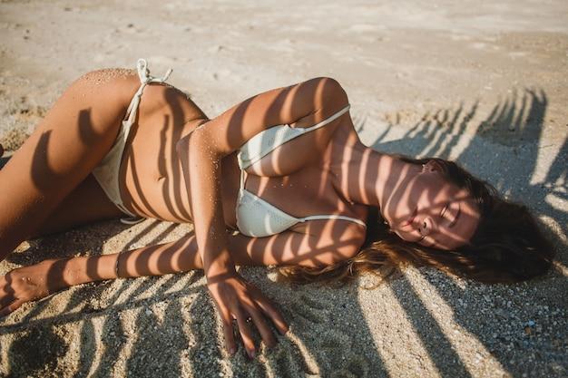 Junge frau, die auf sandstrand unter palmenblatt legt Kostenlose Fotos
