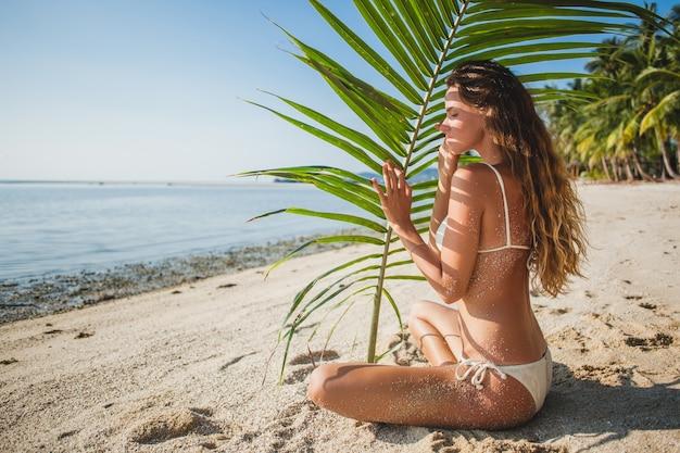 Junge frau, die auf sandstrand unter palmenblatt sitzt Kostenlose Fotos