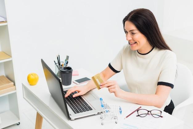 Junge frau, die bei tisch mit kreditkarte mit laptop sitzt Kostenlose Fotos
