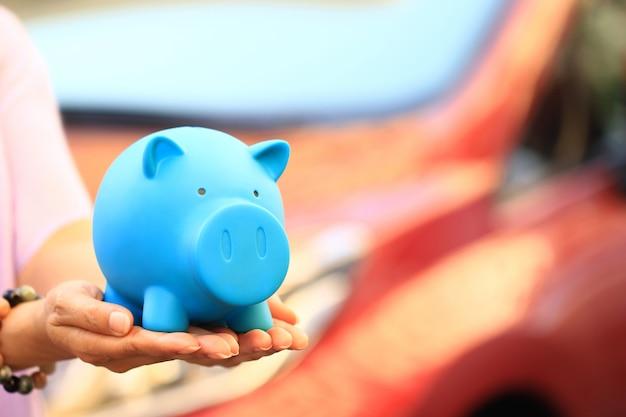 Junge frau, die blaues sparschwein mit der stellung am autoparken hält Premium Fotos