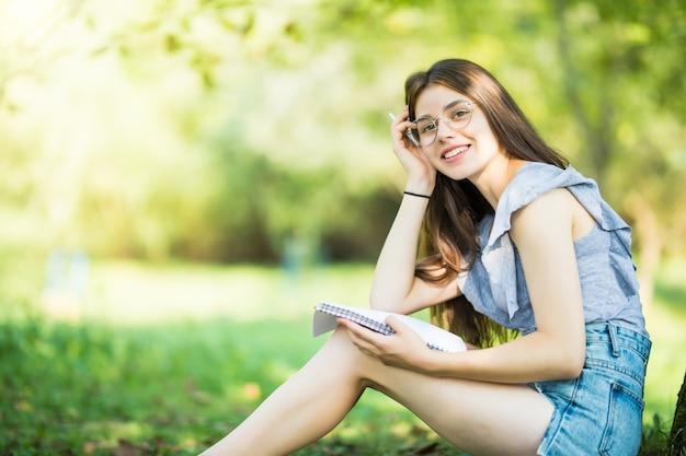 Junge frau, die buch unter dem baum während des picknicks im abendsonnenlicht liest Kostenlose Fotos