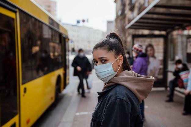 Junge frau, die chirurgische maske draußen an der bushaltestelle in der straße trägt Kostenlose Fotos