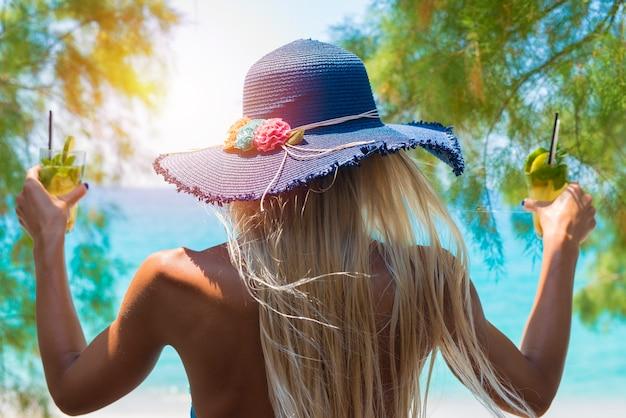 Junge frau, die cocktails in ihren händen am strand hält Kostenlose Fotos