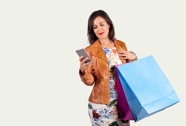 Junge frau, die das mobile und mit einigen einkaufstaschen auf einem weißen hintergrund betrachtet Premium Fotos