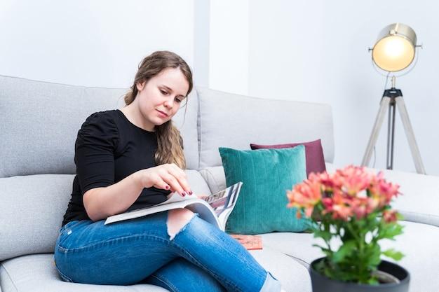 Junge frau, die dekorationsmagazin in ihrem wohnzimmer durchsucht. reformen, lebensstil und innenausstattung. Premium Fotos