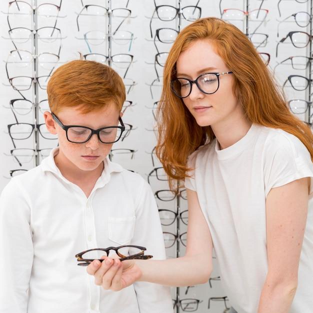 Junge frau, die dem sommersprossenjungen brillen im optikspeicher zeigt Kostenlose Fotos