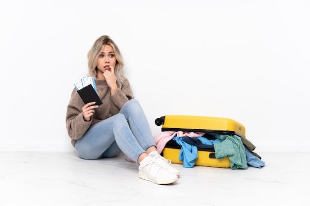 Junge frau, die den boden mit koffer sitzt Premium Fotos