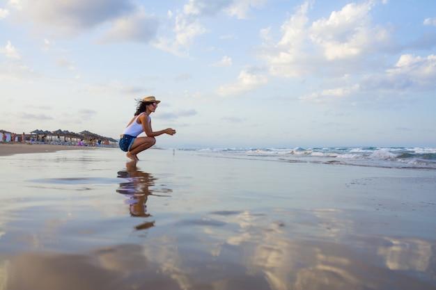 Junge frau, die den ozean erwägt Premium Fotos