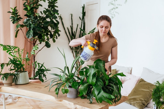 Junge frau, die die pflanzen mit wasserhorisontalrahmen besprüht Premium Fotos