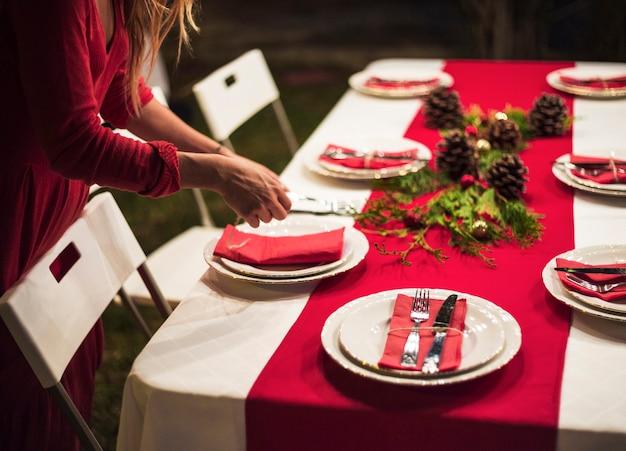 Junge frau, die die tabelle für weihnachtsabendessen einstellt Kostenlose Fotos