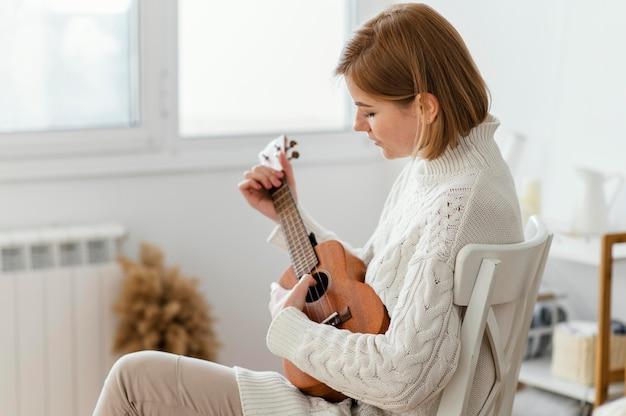 Junge frau, die die ukulele spielt Kostenlose Fotos