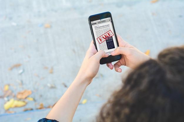 Junge frau, die digitale gefälschte nachrichten auf smartphone liest Premium Fotos