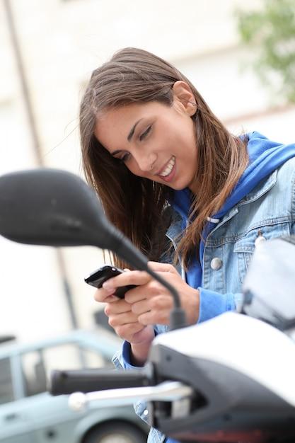 Junge frau, die draußen auf motorrad sitzt Premium Fotos