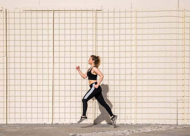 Junge frau, die draußen mit sportkleidung läuft Kostenlose Fotos