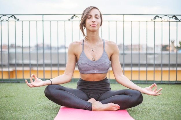 Junge frau, die draußen yoga tut Kostenlose Fotos
