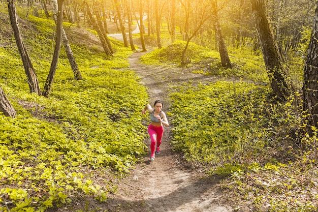 Junge frau, die durch die bäume läuft Kostenlose Fotos